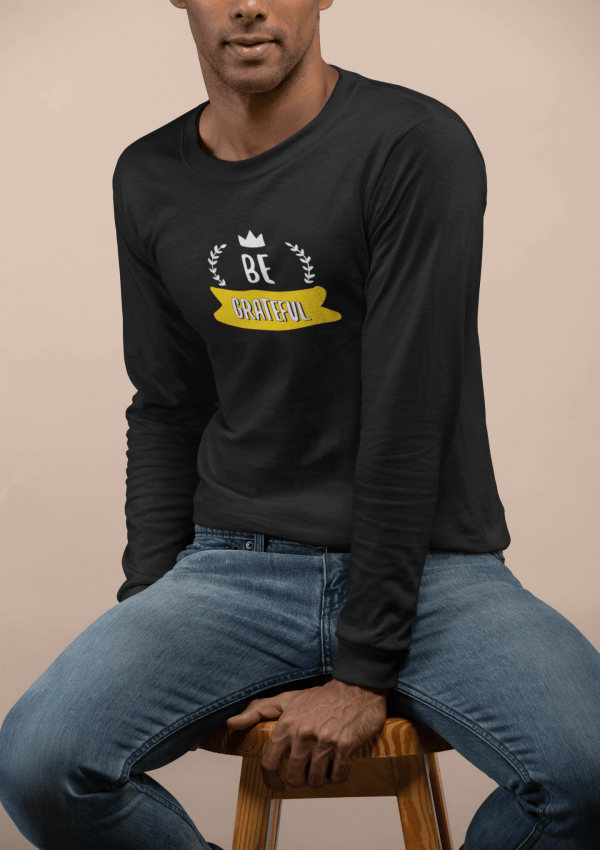 mockup of a man wearing a long sleeve tee sitting on a stool 23324 18