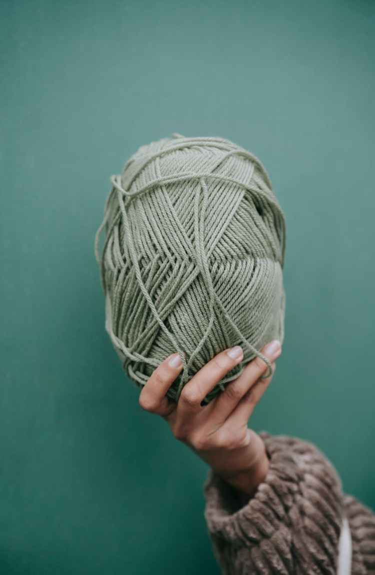 woman in sweater showing ball of yarn against green wall
