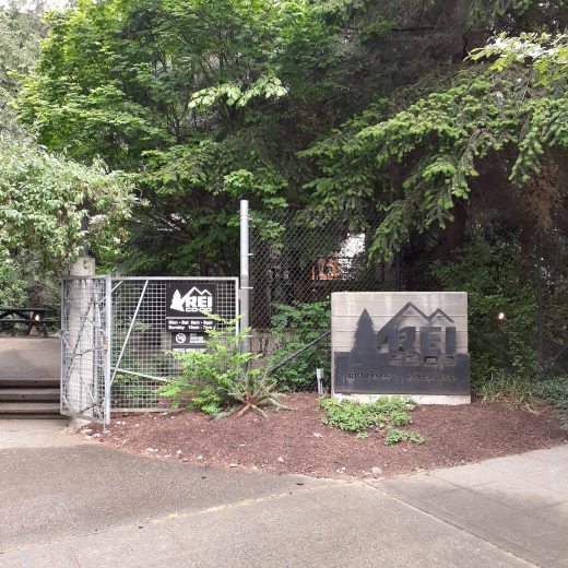 the entrance to rei seattle is wooded with small campground like signs