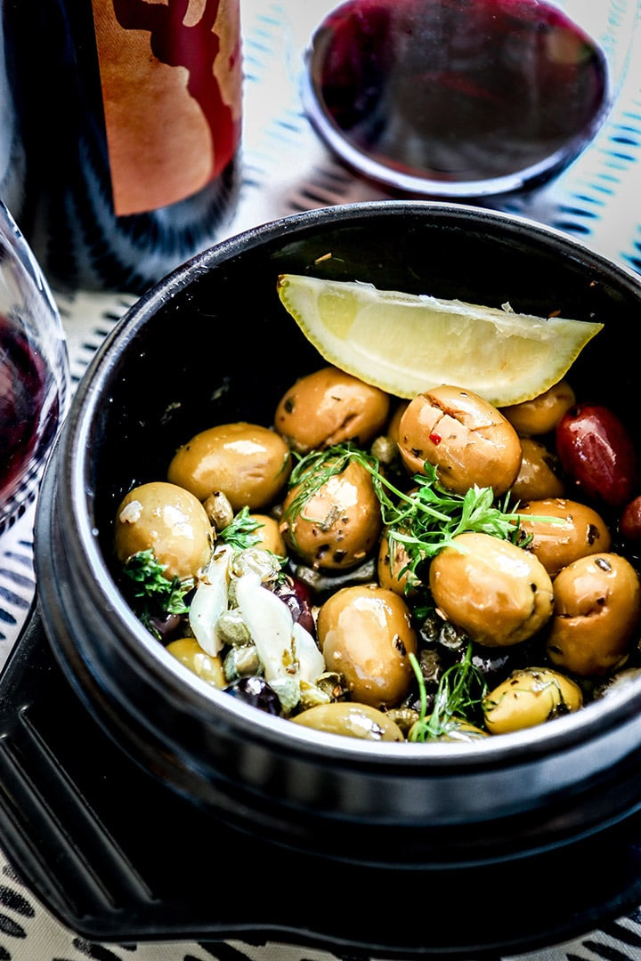Warm marinated olives, garlic + capers with fresh herbs. Heat brings out the flavor in this Spanish-inspired recipe!