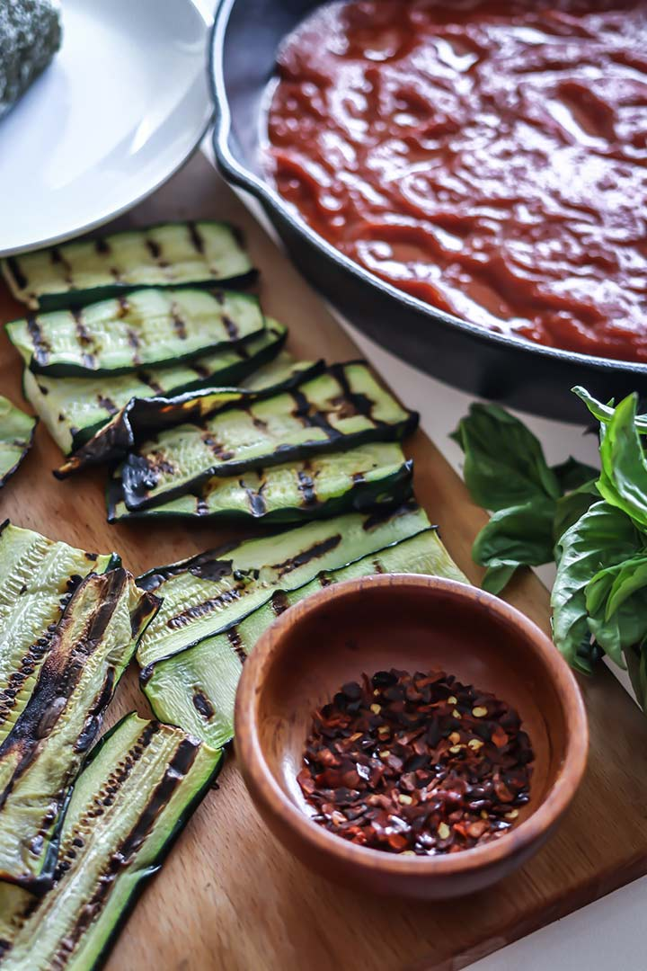 Grilled Zucchini Goat Cheese Bake - zucchini stuffed with herbed goat cheese and baked with marinara sauce. Serve with fresh bread for an easy dinner!