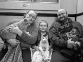 family with young boy adopting two orange cats for kitty's sake