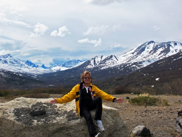 person sitting on a rock with Tombstone mountains in the background
