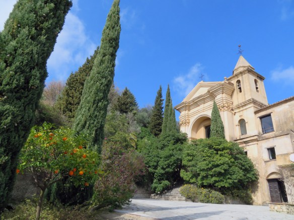 Old church with palm and lemon trees in the foreground