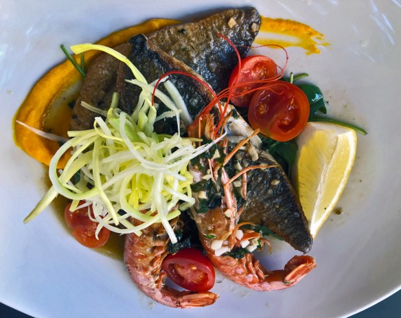 fish fillets with skin on and scampiwith garnishes of tomatoes