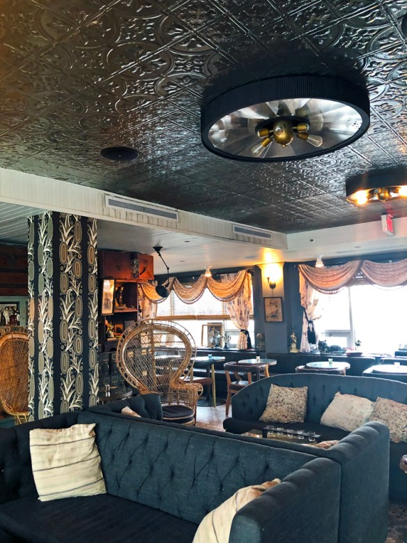 Pressed tin roof, old stuffed chairs, a wicker chair and swagged curtains give Tin Roof bar a very retro feel