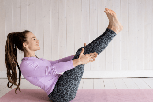 lady wearing purple doing pilates workout at home