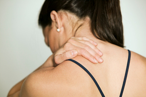 Woman massaging shoulder, in studio, rear view