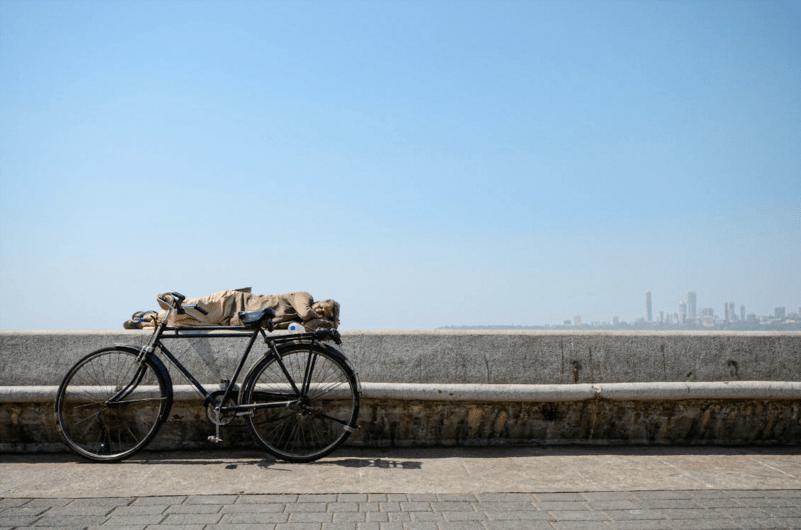 A man has a lunchtime nap along the Bandstand Promenade on the western coast of Mumbai. Mumbai, India