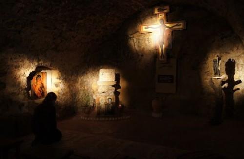 orando en penumbras y en silencio en capilla