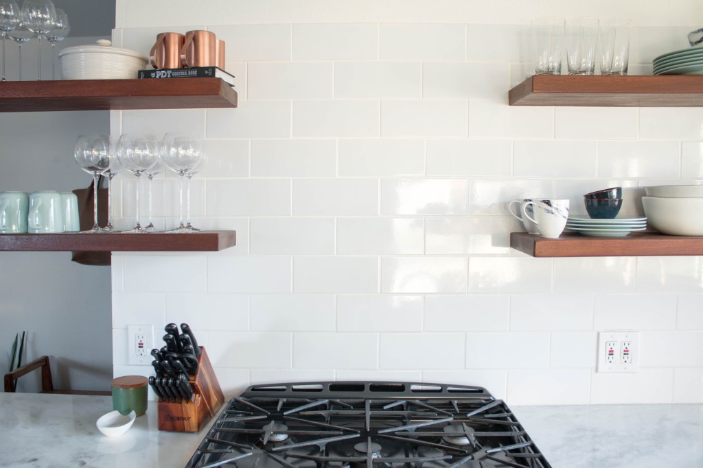Modern kitchen remodel with open wood shelving, marble countertops, and copper accents // via fortheindoorsy.com