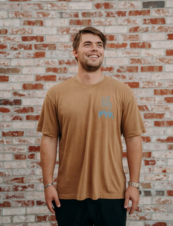 brown tshirt, mens, front chest has two fingers holding peace sign
