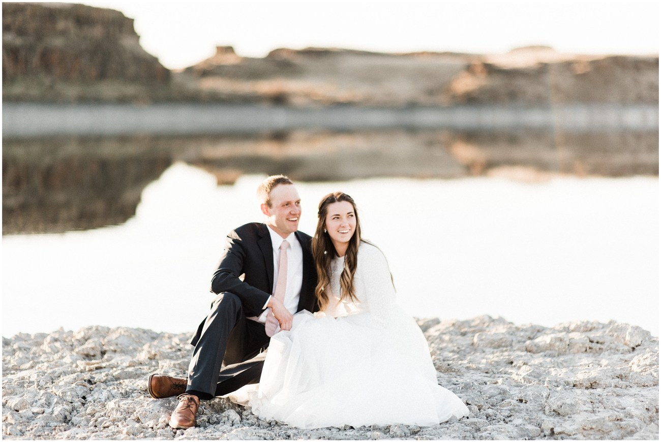 Photo of a bride and groom sitting by a desert lake by Forthright Photo