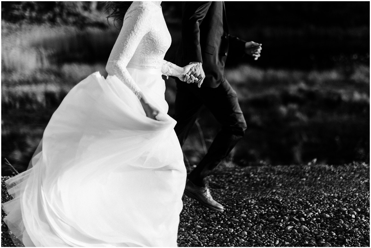 Black and white close up photo of a bride and groom holding hands and running by Forthright Photo