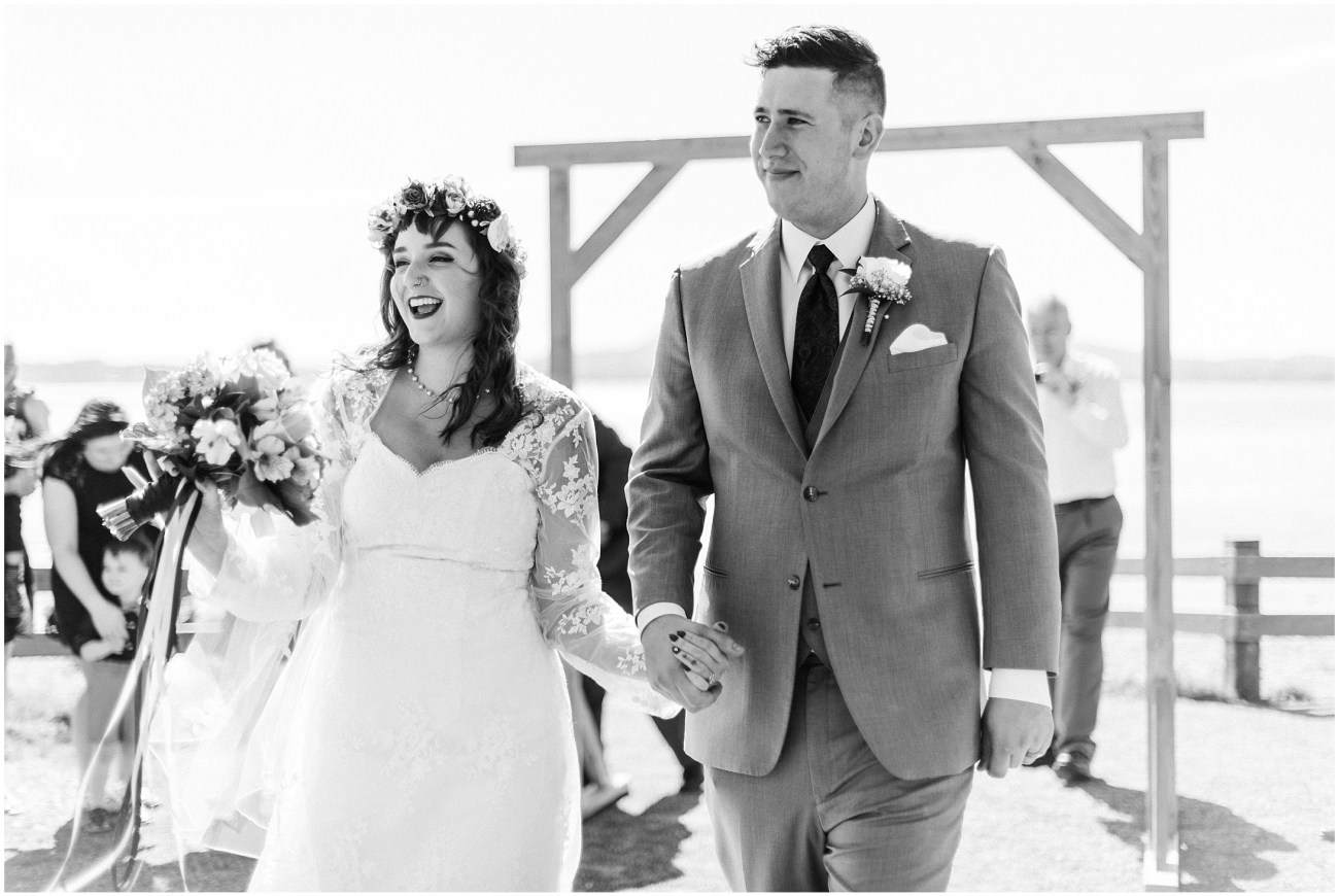 Black and White photo of a bride and groom walking back down the aisle and smiling