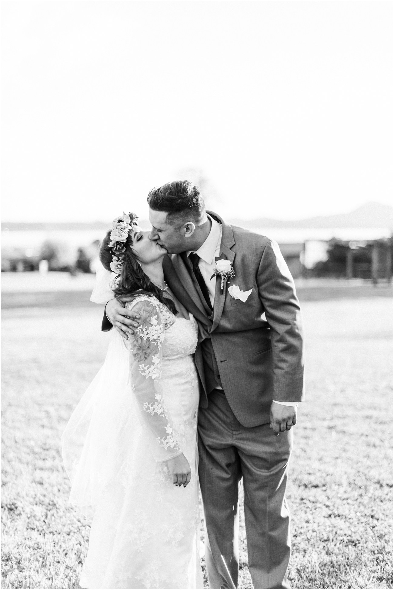 Black and White photo of bride and groom kissing on the lawn of Bayview Civic Hall during their wedding reception in Bayview, WA