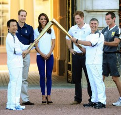 LONDON, ENGLAND - JULY 26: Prince William, Duke of Cambridge, Catherine, Duchess of Cambridge and Prince Harry watch Wai-Ming hand over the London 2012 Olympic Torch to John Hulse during a visit to Buckingham Palace during Day 69 of the London 2012 Olympic Torch Relay on July 26, 2012 in London, England. The Olympic flame is making its way through the capital on the penultimate day of its journey around the UK before arriving in the Olympic Stadium on Friday evening for the Olympic games' Opening Ceremony. (Photo by Ian West - WPA Pool/Getty Images)