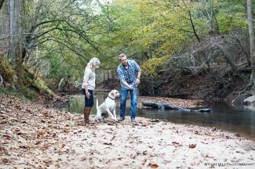 Couple playing with dog in creek