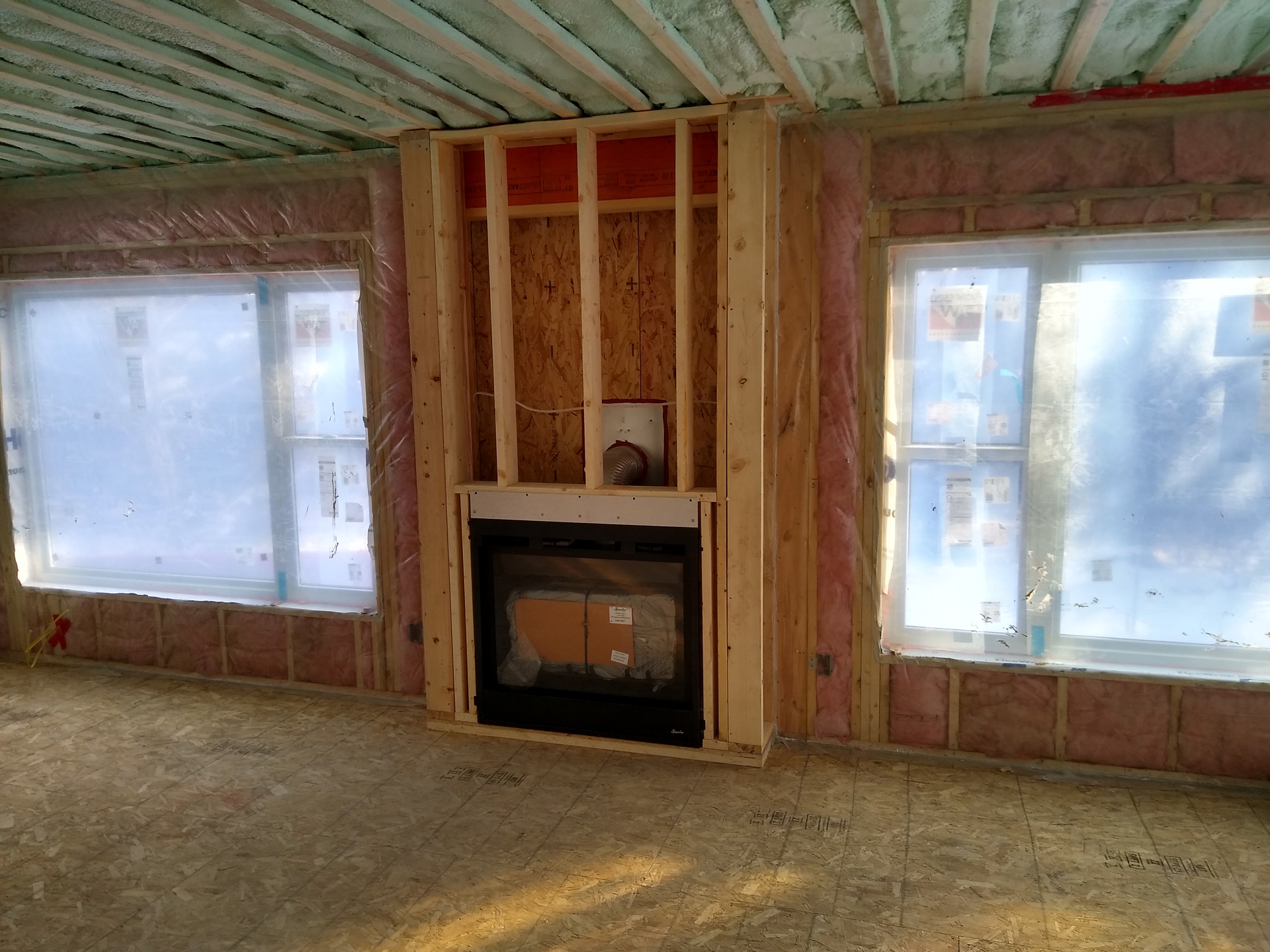 fireplace with windows on side and unfinished walls