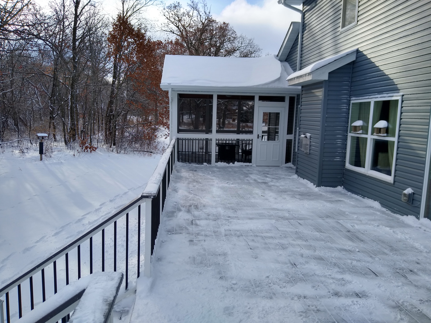 deck with 2 season porch with snowy ground