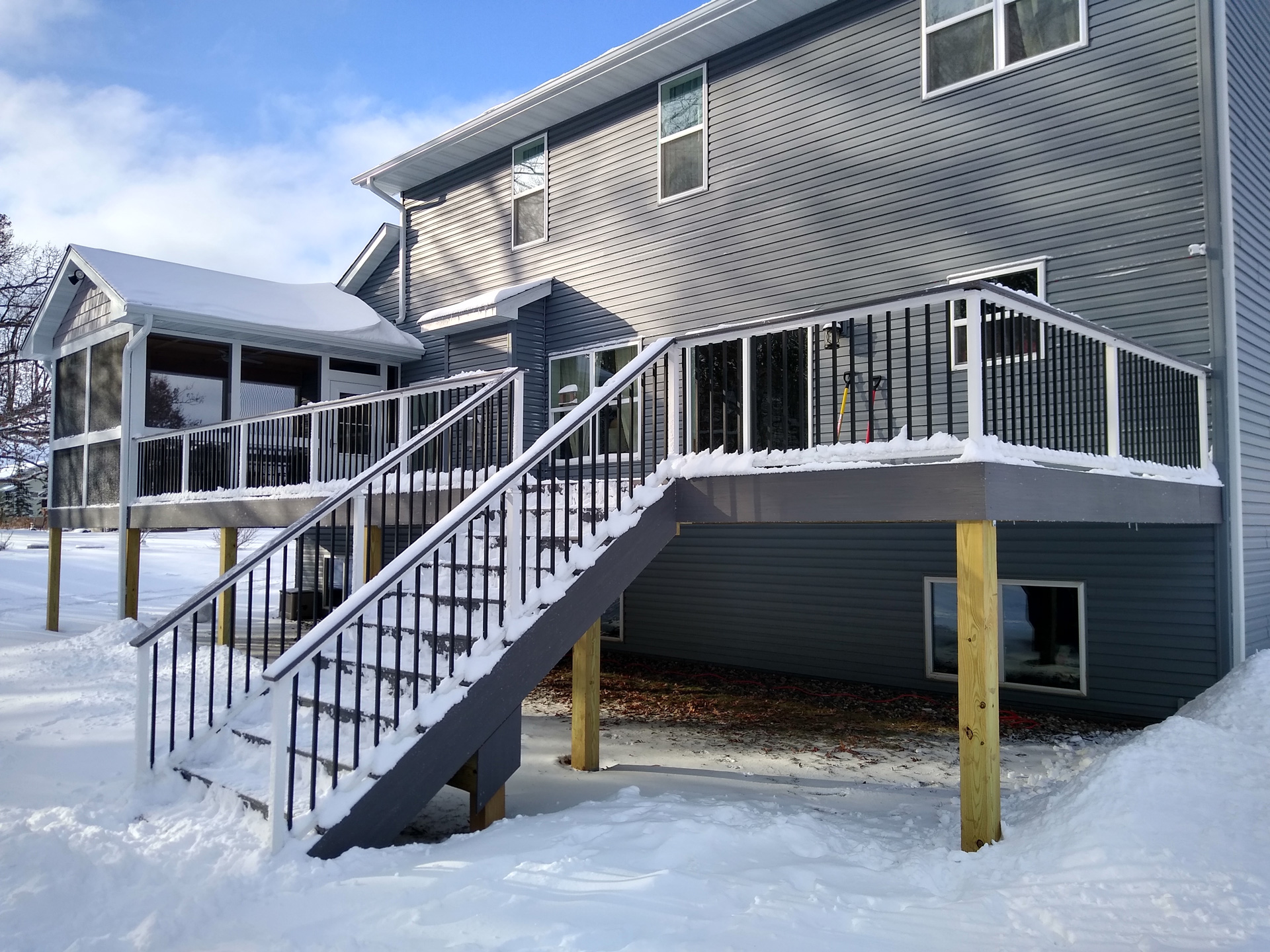 large deck with metal railing and gray house with snow on deck
