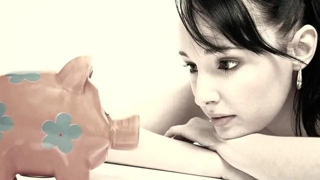 豚の貯金箱を見る女性 貯金 金運