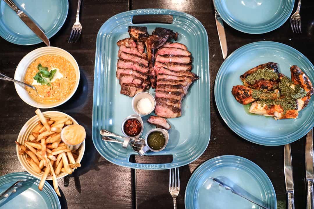 Ultra dry-aged porterhouse steak, wood fire grilled half chicken from Charbar Calgary