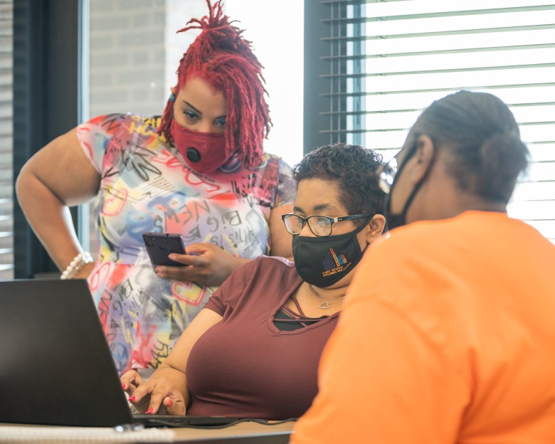 Two Fort Worth Housing Solutions employees (left) help a resident of Columbia Renaissance Square work through an application for Rental Assistance.