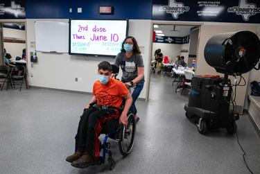 Joshua Martin, 17, is pushed by his mother Teddi Martin after they received their first dose of a COVID-19 vaccine at McKinney ISD Stadium and Community Event Center on May 20, 2021.