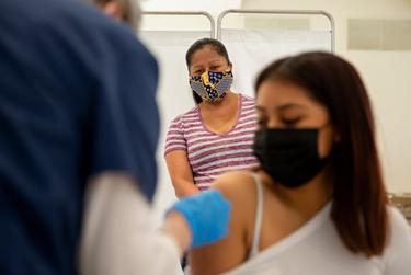 Maria Campos watches her daughter Vicky Martinez receive the COVID-19 vaccine at the Tennison Memorial United Methodist Church in Mt. Pleasant on May 7, 2021.