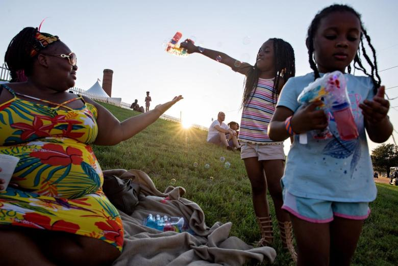 """Brianna Williams plays with her daughters Hope and Faith during the """"I Am Juneteenth"""" festival at the Panther Island Pavilion in Fort Worth on June 19, 2021."""