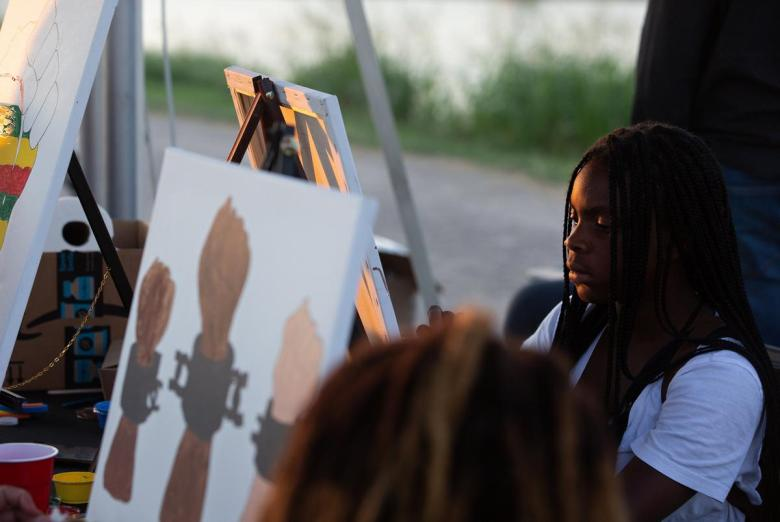 Trineese Potter paints at the Creative Tingz shop stand during the I Am Juneteenth festival at the Panther Island Pavilion in Fort Worth on June 19, 2021.