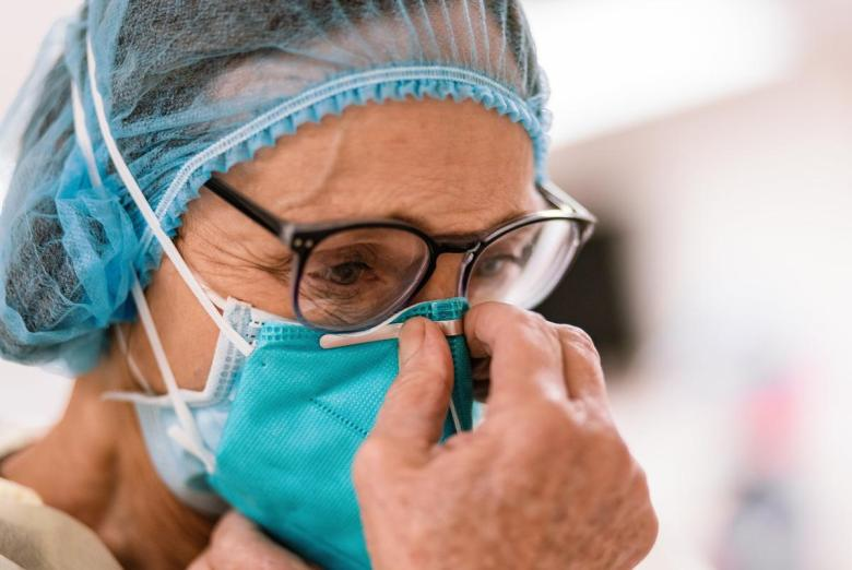 Registered Nurse Lori Kelley dons an N95 mask and other PPE before entering the room of a COVID-19 patient at Goodall-Witcher Hospital in Clifton on Wednesday, August 3, 2021.