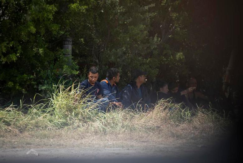 A group of migrants wait near a private road after being apprehended by Department of Public Safety officers at a train depot in Spofford on Aug. 25, 2021.