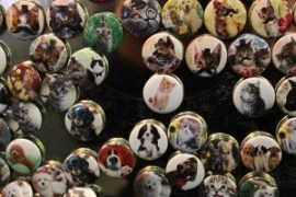A photo of buttons with mustachioed cats on them.