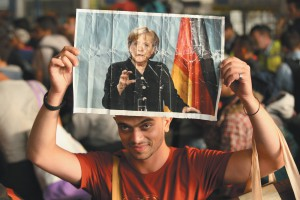 A Syrian refugee holding a picture of German Chancellor Angela Merkel as he and hundreds of other migrants and refugees arrived in Munich from Hungary, September 2015