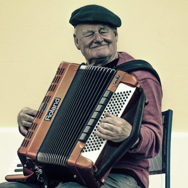 Abbildung eines älteren Mannes mit Akkordeon