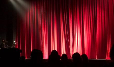 Públic en una sala de teatre amb teló tancat