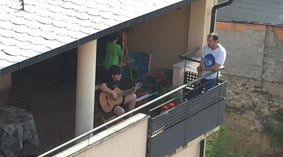 Un jove tocant la guitarra des d'un balcó