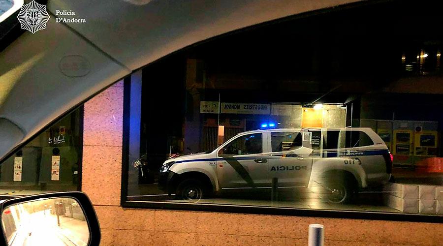 Un vehicle de policia reflectit en el vidre d'un establiment,.