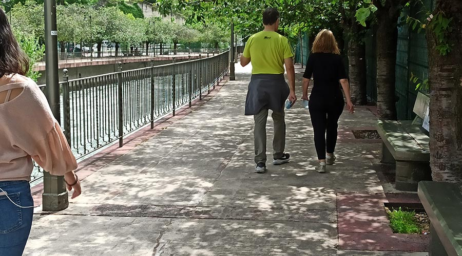 Gent al passeig del riu amb la mascareta a la mà