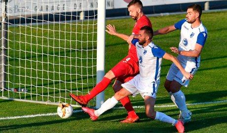 Emili Garcia del Inter Club Escaldes lluita una pilota davant dos jugadors del Drita de Kosovo