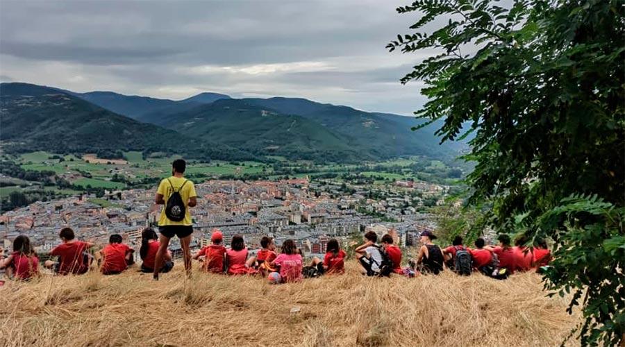 Un grup de nens descansa després d'una excursió per veure la Seu d'Urgell des d'un punt elevat