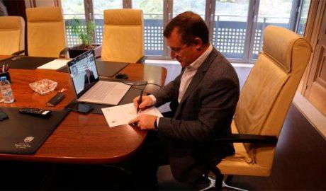 El cònsol major de Sant Julià de Lòria, Josep Majoral, signa un compromís de manera telemàtica amb i el president de l'Institut de Turisme Responsable, el doctor Tomás Azcárate, que està a la pantalla. Foto: Comú de Sant Julià de Lòria