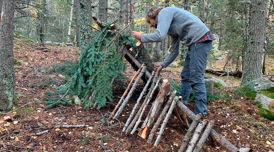 Una persona construeix una estructura amb troncs i branques