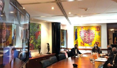 Els consellers d'Encamp en una pantalla i els cònsols, amb l'interventor i el secretari, en un despatx, celebrant una sessió del Consell de Comú