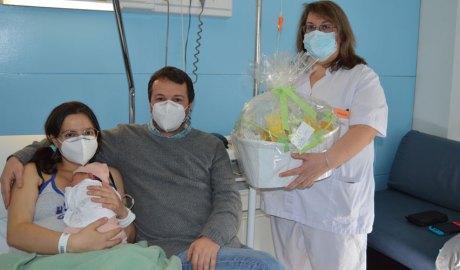 L'Abril, el primer nadó del 2021, amb els seus pares Maria José i David, i la professional del SAAS que els entrega una cistella