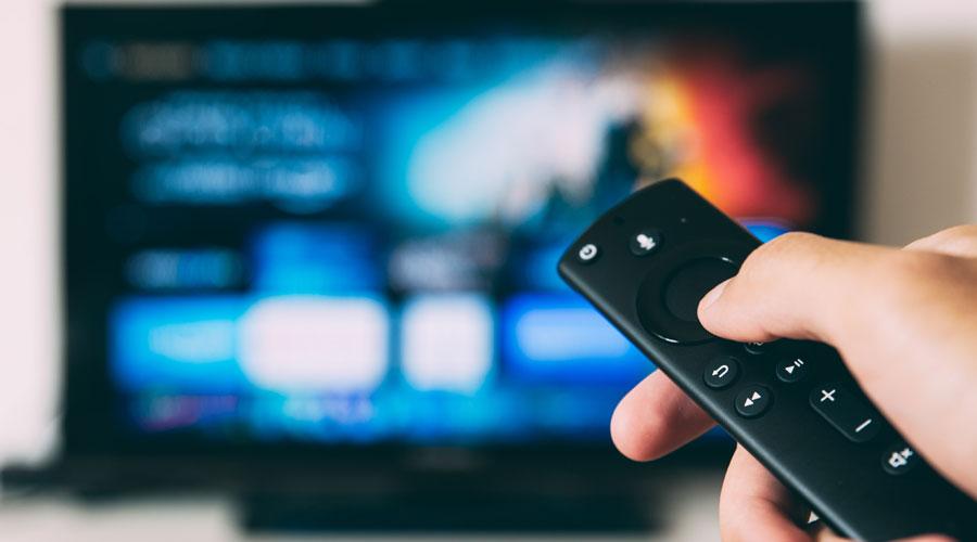 Una persona fent ús del control remot de la televisió.