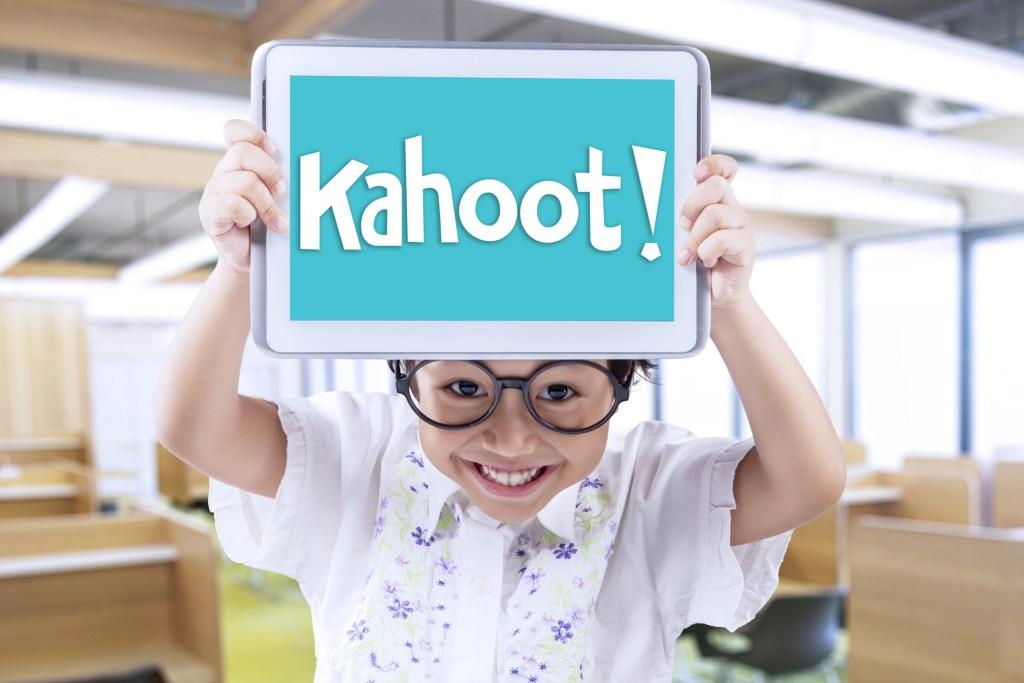valoración formativa - chico levantando tableta con la palabra Kahoot
