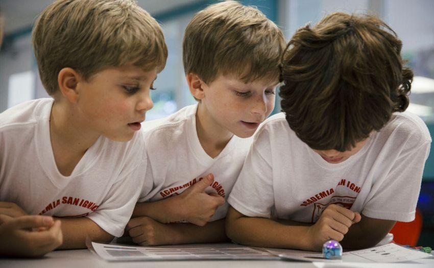 Niños reunidos a un mini robot